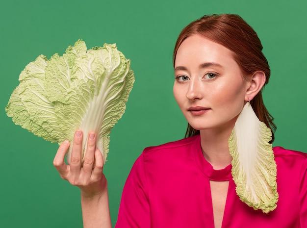 Bello ritratto della donna della testarossa con la verdura