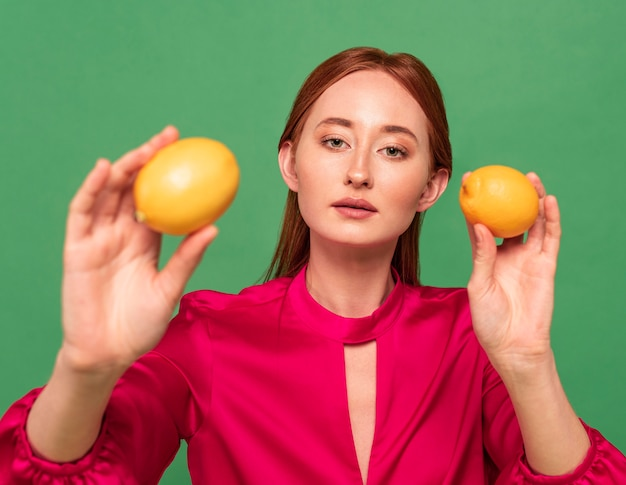 Красивая рыжая женщина позирует с фруктами