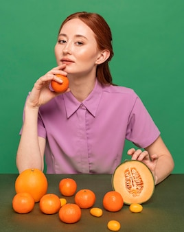 Красивая рыжая женщина позирует с апельсинами