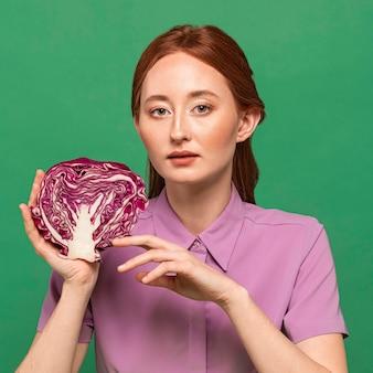 Bella donna della testarossa che posa con la verdura