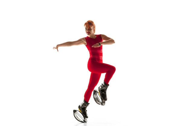 Beautiful redhead woman in a red sportswear jumping in a kangoo jumps shoes