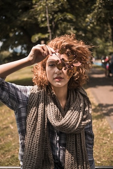 Beautiful redhead woman in scarf holding leaves