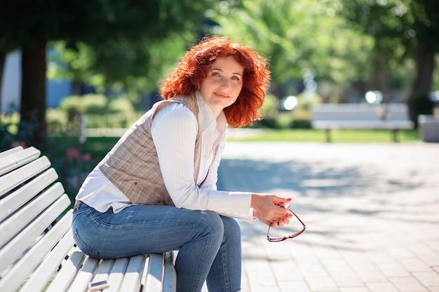 Красивая рыжая женщина сидит на скамейке в парке в солнечный летний день и наслаждается жизнью
