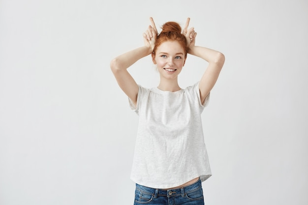 Beautiful redhead woman smiling showing hare hands.