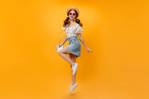 Beautiful redhead woman in summer denim outfit and straw hat holding white bag and jumping on orange background.