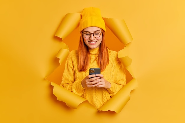 Beautiful redhead woman uses mobile phone surfs social networks has good mood dressed in yellow hat and sweater breaks through paper hole