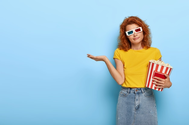 Beautiful redhead woman wears virtual glasses, yellow t shirt and denim skirt, holds basket of popcorn, comes in cinema, has doubtful expression, hesitates which film to choose for watching.