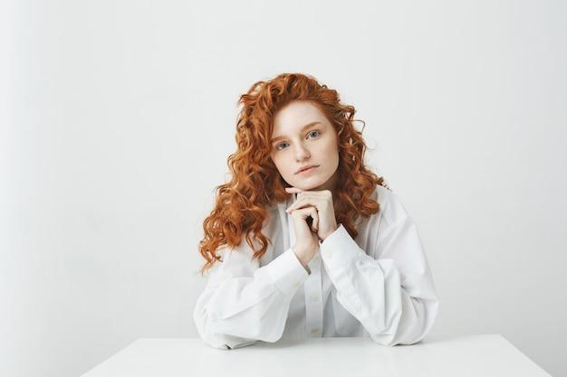 白い表面の上のテーブルに座ってカメラを見て巻き毛の美しい赤毛の女性