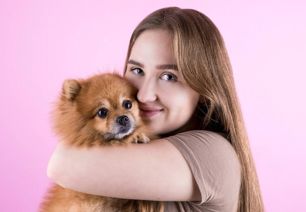 Beautiful redhead young woman hugs and kisses her puppy spitz dog. love between dog and owner
