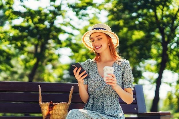 Pを使用して手にコーヒーを持って都市公園のベンチでリラックスした美しい赤毛の若い女性...