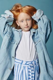 Красивая рыжеволосая девочка с длинными волосами в большой синей длинной джинсовой куртке. модная одежда, весенний портрет красной девушки на синем фоне. большие красивые глаза молодой девушки, яркий портрет