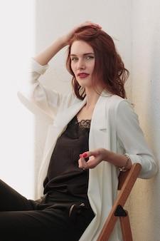 美しいredhear女性の白いジャケット、ハイヒール、そしてバルコニーに座っている黒いシャツ