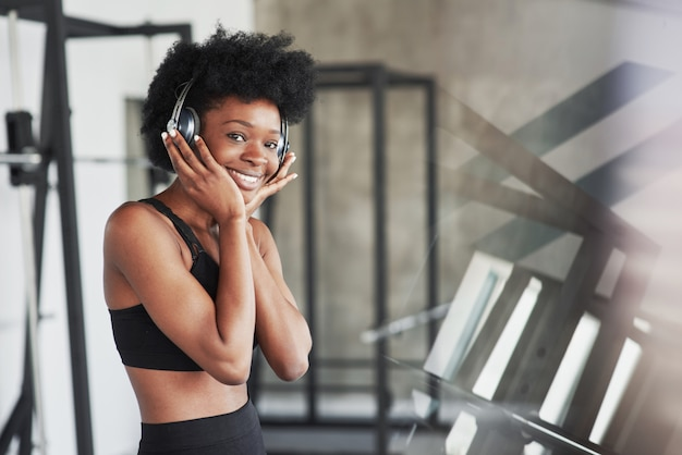 Beautiful reflection. african american woman with curly hair and in sportive clothes have fitness day in the gym