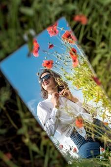 ポピー畑の鏡の中の少女の美しい反射。夏時間