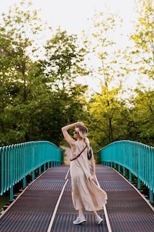 橋の上で動きながらポーズをとって、ドレスを着て美しいリラックスした金髪の若い女性。