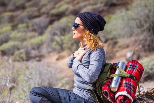 아름 다운 편안한 백인 성인 여성 휴식 시간 동안 야외에서 일부 영기 및 명상 활동을 doink 트레킹 하이킹에서 휴식-대체 사람들의 라이프 스타일 건강한 생활