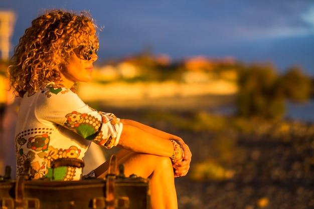 오래 된 수하물과 함께 바다 앞에 앉아 흰 드레스와 아름 다운 편안한 백인 아가씨. 여행하고 라이프 스타일 컨셉을 즐기십시오. 여름철 휴가 휴가의 좋은 사람과 자연.
