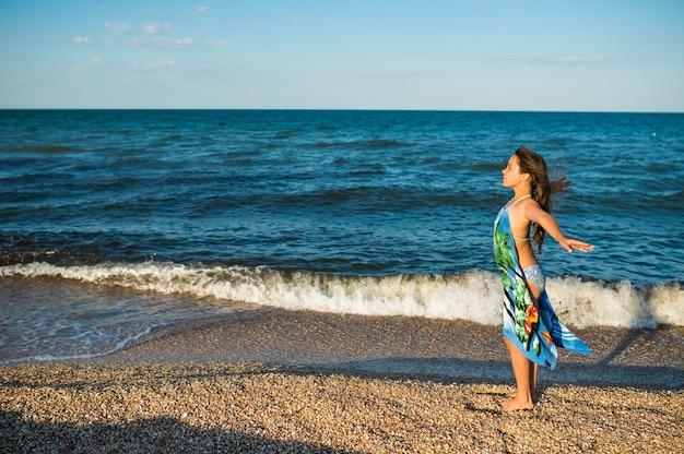 Красивая расслабленная женщина отдыхает на пляже у моря с шарфом в солнечный теплый летний день.