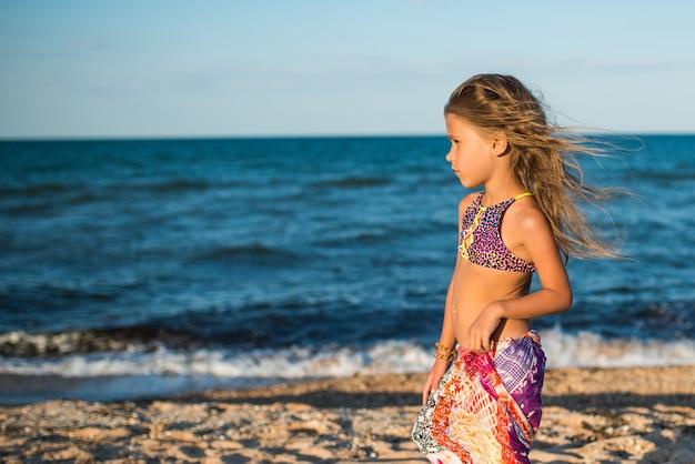 화창한 따뜻한 여름날에 스카프와 함께 바다 해변에서 쉬고 아름다운 편안한 여자