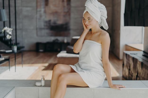 フェイスクリームを塗るタオルに包まれた美しいリラックスした女性