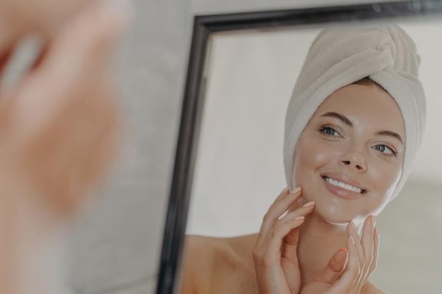 Красивая расслабленная женщина, обернутая полотенцем, применяя крем для лица