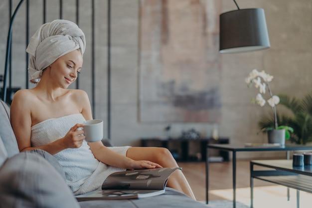 Красивая расслабленная женщина, завернутая в полотенце, пьет чай