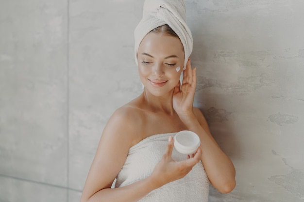 Beautiful relaxed woman wrapped in towel applying face cream