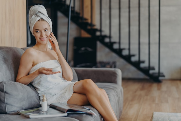 Beautiful relaxed woman wrapped in towel drinking tea