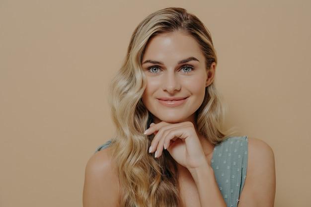 Красивая расслабленная молодая блондинка в синем платье с рукой под подбородком смотрит в камеру с оптимизмом, удовлетворением и легкой улыбкой, стоя изолированно рядом с оранжевой стеной