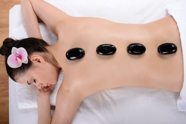 Beautiful relaxing woman with stones on her back in a spa.