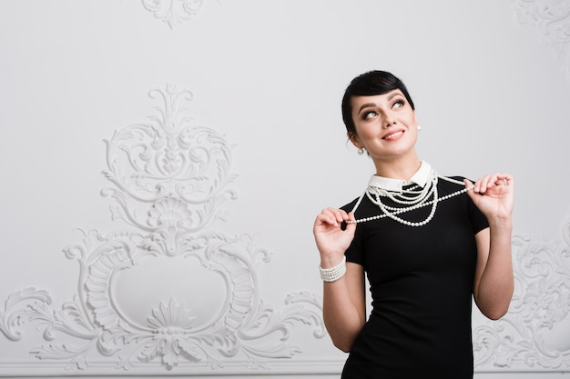 Красивая ретро женщина с жемчужным ожерельем в роскошном интерьере