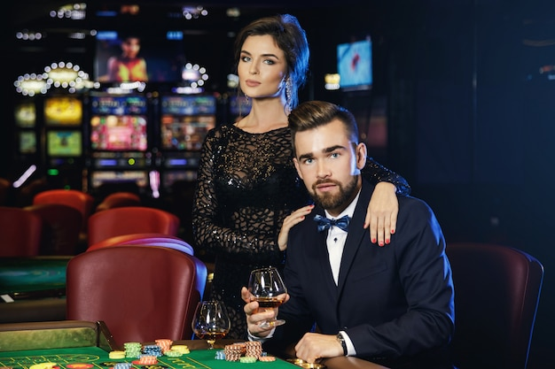 Beautiful and rich couple playing roulette in the casino
