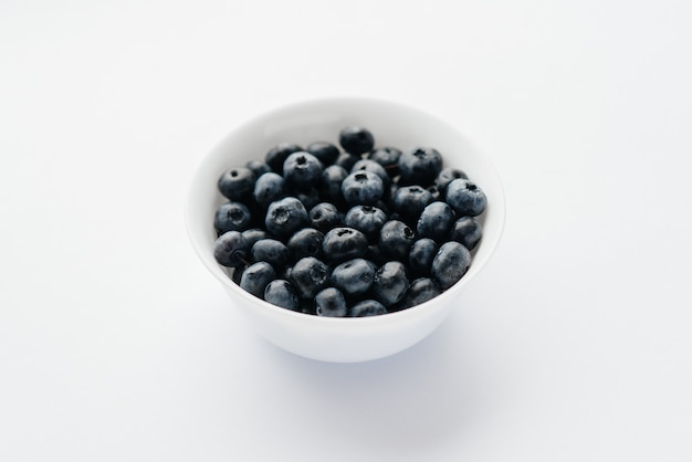 Beautiful ripe blueberries in a glass bowl on a white background. healthy food, and vitamins.