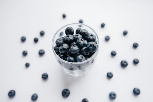 白い背景の上の透明なガラスガラスの美しい熟したブルーベリー。健康食品、そしてビタミン。