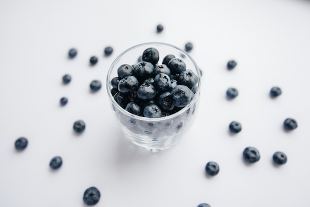 Beautiful ripe blueberries in a transparent glass glass on a white background. healthy food, and vitamins.