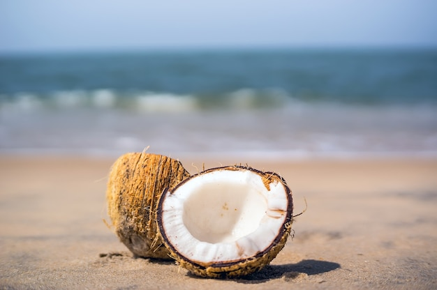 Красивый спелый кокос, разбитый на две части, лежит на белом песчаном пляже на размытом фоне синего моря и голубого неба с облаками