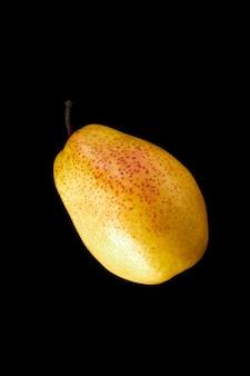 Beautiful ripe yellow pear on black surface