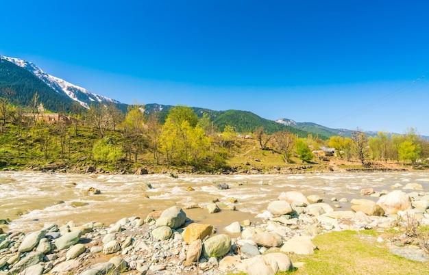 カシミール州、インドの美しい川と雪の山々の景観。