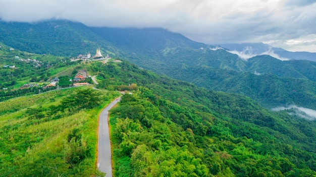 Beautiful road and hills village under the sea of clouds in thailand.
