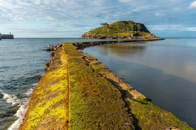 Красивая дорога на остров сан-николас во время отлива от пляжа исунца в лекейтио, страна басков