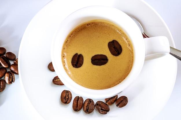 白いカップに温かい淹れたてのコーヒーと美しい焙煎コーヒー豆