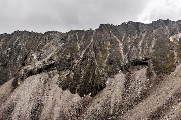 Красивый рок на фоне облачного неба. вертикальная каменная стена. много каменных осыпей. по горизонтали.