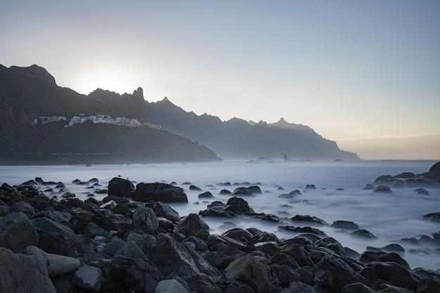 Красивые скалы на пляже у туманного моря с горами