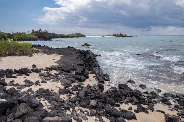 エクアドルの波状の海のそばの美しい岩のビーチ