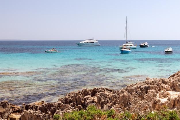 Красивое скалистое побережье и бирюзовое море с лодками на ибице, испания