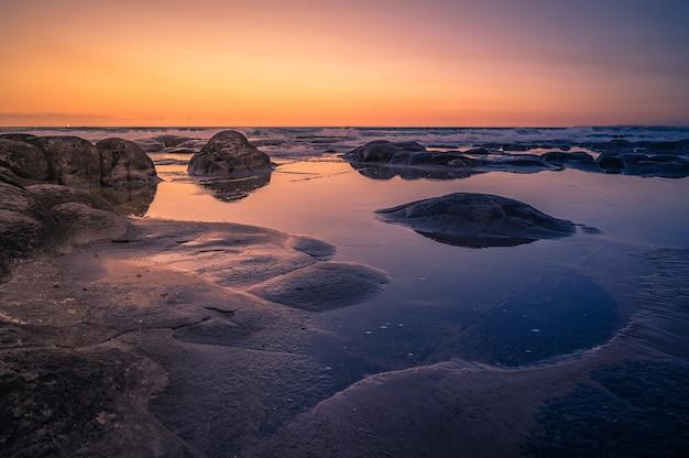 日没時のオーストラリア、クイーンズランド州の美しい岩の多い海岸