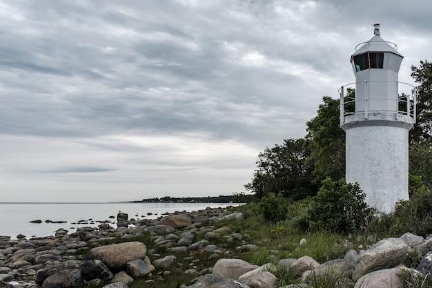 Красивый скалистый берег моря с белой башней маяка на стороне