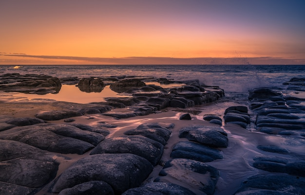 Beautiful rocky coast in queensland, australia on sunset
