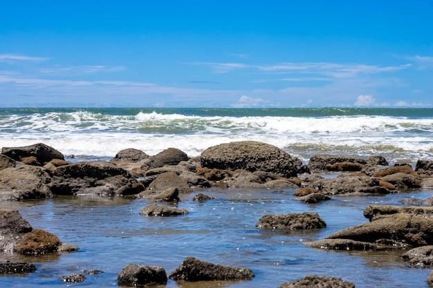 푸른 하늘과 파도 풍경이 보이는 아름다운 바위 해변