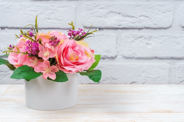 텍스트에 대 한 공간을 가진 흰색 벽돌 벽 배경에 whtie 라운드 꽃병에 핑크 장미의 아름 다운 로맨틱 꽃다발. 발렌타인 데이, 결혼식 개념.